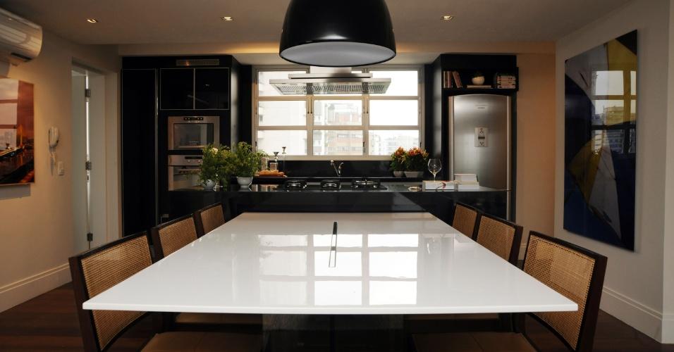 O projeto da arquiteta Marta Sá Oliveira trabalhou com simetrias, de modo que a mesa de jantar (Brentwood) fica centralizada em relação à ilha de cocção. O móvel acomoda sete comensais com conforto nas cadeiras de madeira e palhinha (Vermeil). A noite, o pendente clareia a área para refeições e, durante o dia, a luz natural é abundante e provém da ampla janela