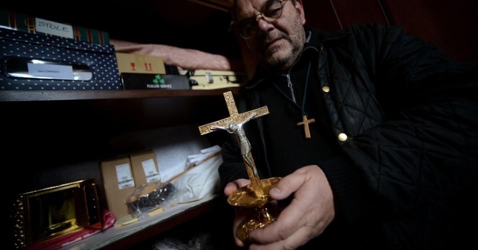 9.jan.2013 - Padre Lorenzo Pasquotti mostra um crucifixo encontrado no navio Costa Concordia, que naufragou em 13 de janeiro de 2012. O acidente deixou 32 mortos. Um ano após o naufrágio, os restos do navio se transformaram em ponto turístico para a pequena ilha, que recebe muitos visitantes que desejam tirar fotos em frente à embarcação