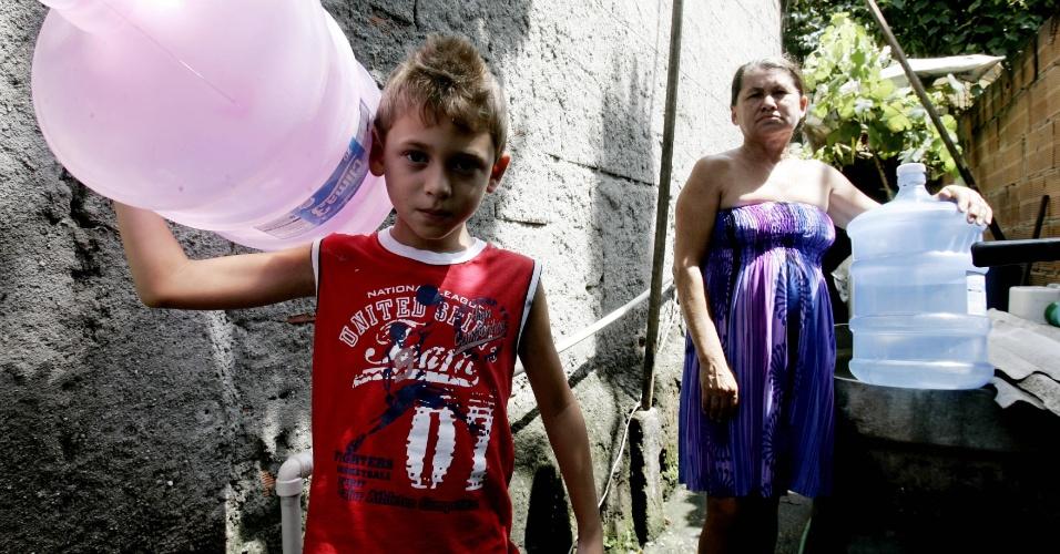 9.jan.2013- Maria das Neves, 53, moradora do bairro Jardim da Viga, em Nova Iguaçu, no Rio de Janeiro, carrega galões de água com o neto, Caio. Devido aos estragos provocados pelas chuvas na região, os moradores do bairro sofrem com a falta de água