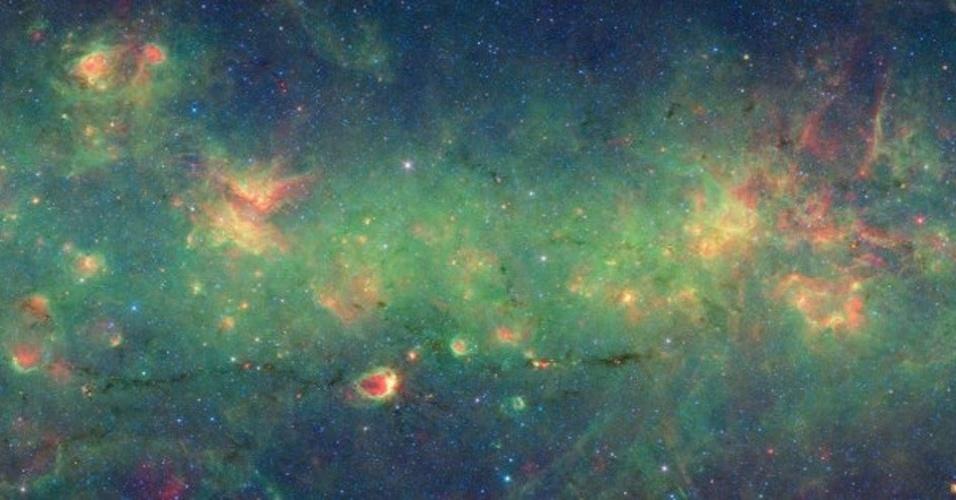 10.jan.2013 - Uma faixa de gás frio e poeira no pé desta imagem do telescópio Spitzer se parece com a silhueta de uma cobra. A nuvem escura em infravermelho tem mais de 300 anos-luz de comprimento, mas apenas alguns de largura e está localizada entre os dois braços em espiral de nossa Via Láctea, algo em torno de 10 mil anos-luz da Terra