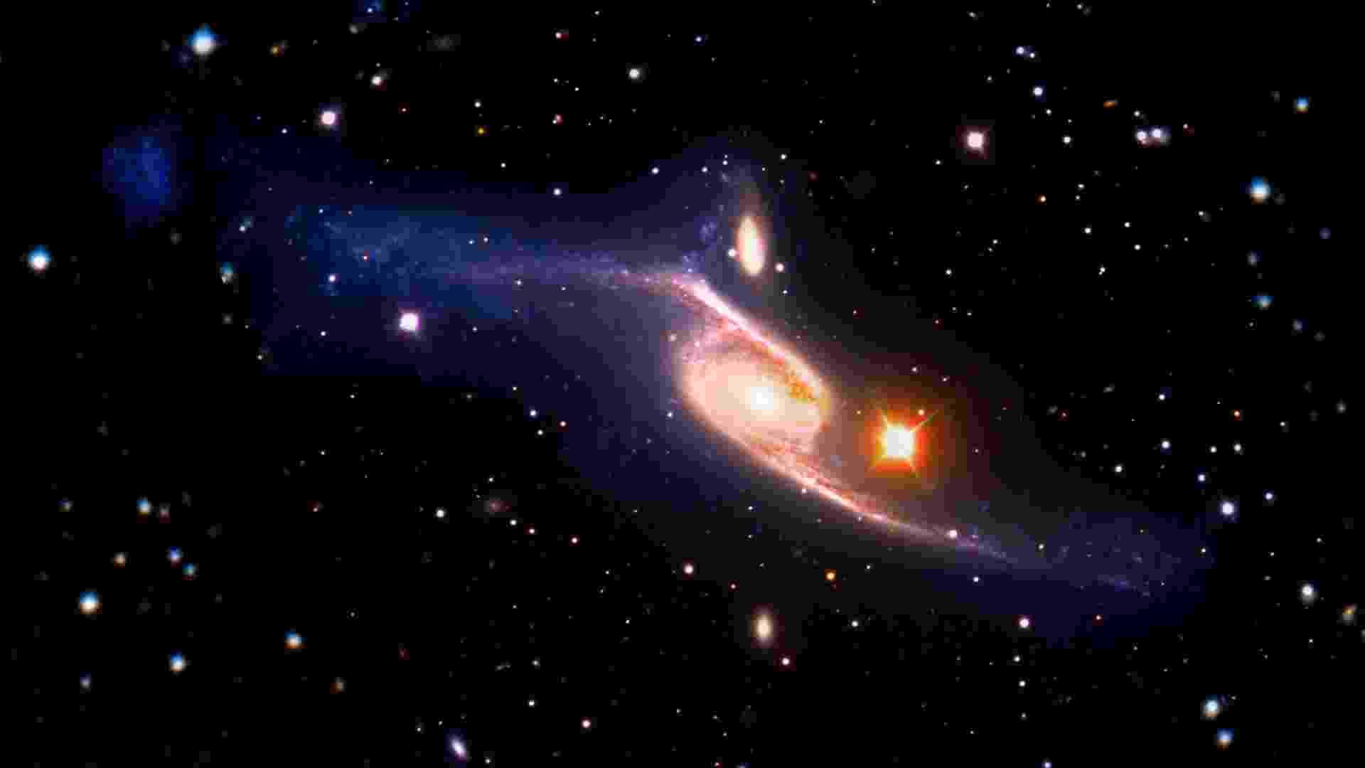 11.jan.2013 - O satélite Galex captou, por acidente, a maior galáxia em espiral já registrada por astrônomos. Segundo estimativas, a NGC 6872 fica a 212 milhões de anos-luz da Terra e tem um tamanho cinco vezes maior que a nossa Via Láctea. Os astrônomos dizem que a descoberta recorde resulta de uma colisão com a IC 4970, uma galáxia vizinha - Nasa's Goddard Space Flight Center/ESO/JPL-Caltech/DSS