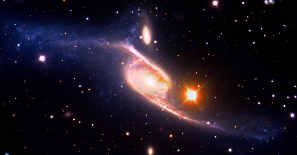 11.jan.2013 - O satélite Galex captou, por acidente, a maior galáxia em espiral já registrada por astrônomos. Segundo estimativas, a NGC 6872 fica a 212 milhões de anos-luz da Terra e tem um tamanho cinco vezes maior que a nossa Via Láctea. Os astrônomos dizem que a descoberta recorde resulta de uma colisão com a IC 4970, uma galáxia vizinha