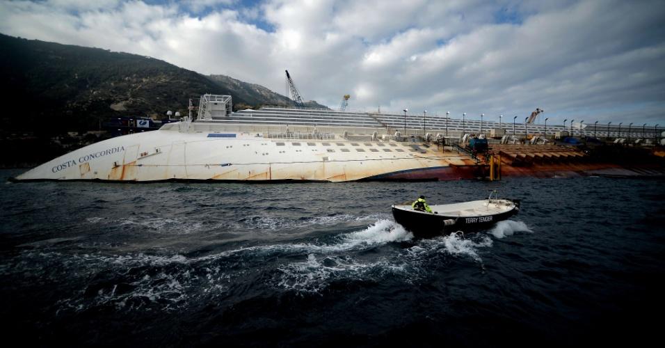 12.jan.2013 - Barco passa ao lado dos destroços do navio Costa Concordia, na ilha de Giglio, na Itália.