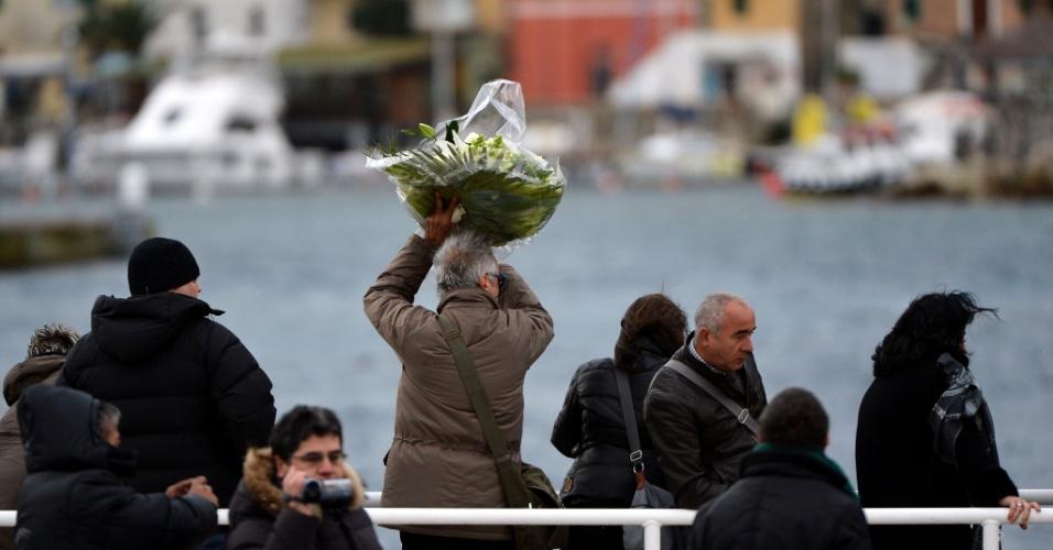13.jan.2013 - Homem joga buquê de flores ao mar em homenagem aos mortos no acidente com o navio Costa Concordia. Após um ano do naufrágio que deixou 30 mortos e dois desaparecidos na costa italiana, o navio continua atracado no mesmo lugar e deve demorar para ser retirado