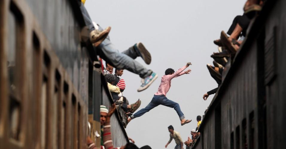 13.jan.2013 - Homem se arrisca pulando de um trem para outro durante comemoração religiosa em Bangladesh