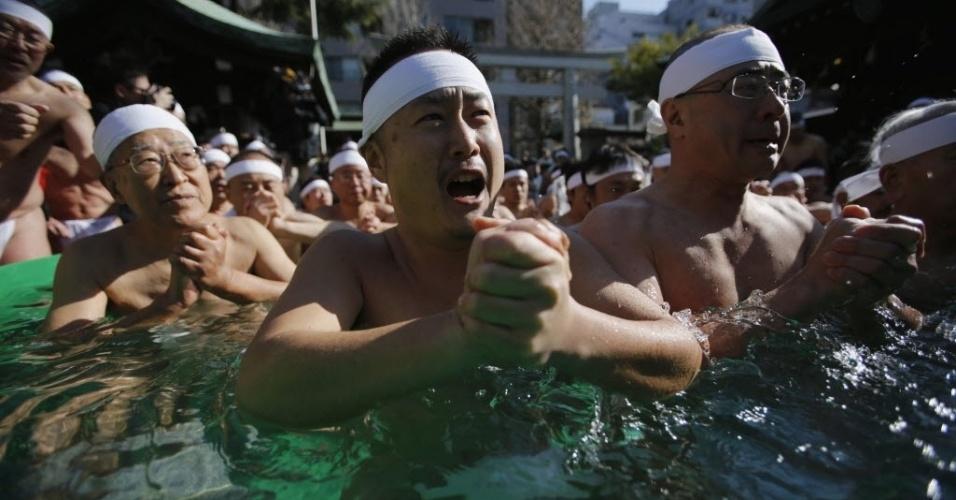 13.jan.2013 - Homens vestidos apenas com cuecas rezam dentro de água gelada no santuário de Teppozu, em Tóquio (Japão). Cerca de 90 pessoas participam da cerimônia Shinto para purificar suas almas e fazer preces por uma boa saúde no ano ano