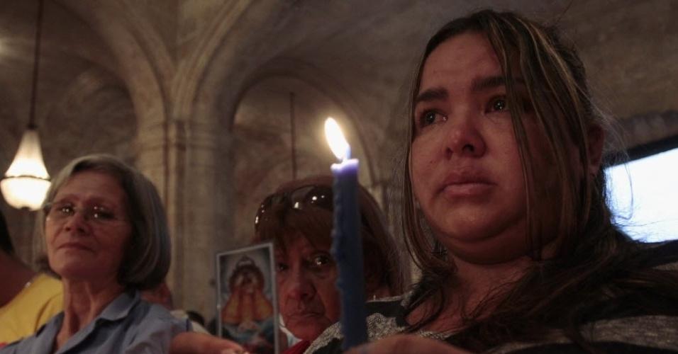 13.jan.2013 - Mulher segura vela durante missa celebrada pela recuperação do presidente da Venezuela, Hugo Chávez, em Havana (Cuba)