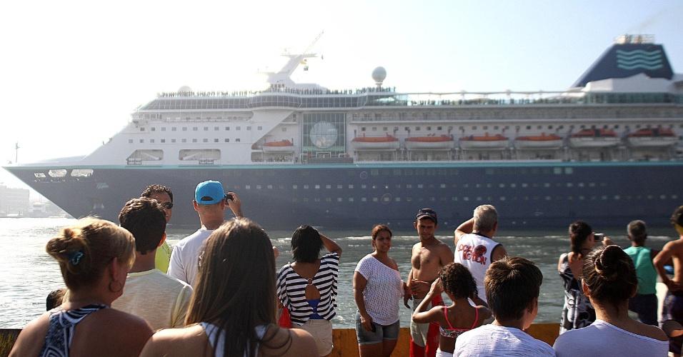 13.jan.2013 - Turistas observam passagem de cruzeiro na travessia de balsas em Santos, no litoral de São Paulo