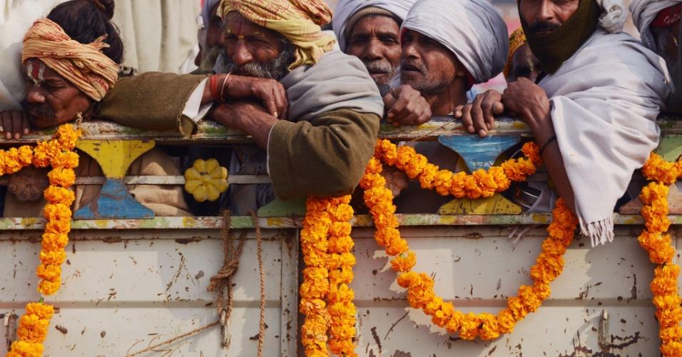 14.jan.2013 - Devotos hindus  pegam carona na traseira de um caminhão durante o festival Kumbh Mela em Allahabad, na Índia, um dos maiores do mundo
