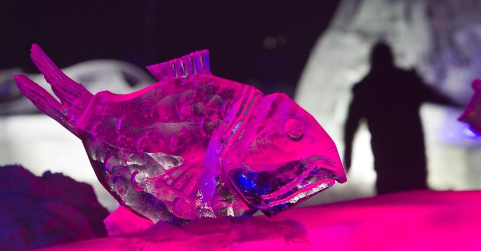 14.jan.2013 - Homem caminha por trás de obra de gelo em formato de peixe em Almaty, no Cazaquistão, no festival Eight Lakes, que traz diversas obras esculpidas em gelo
