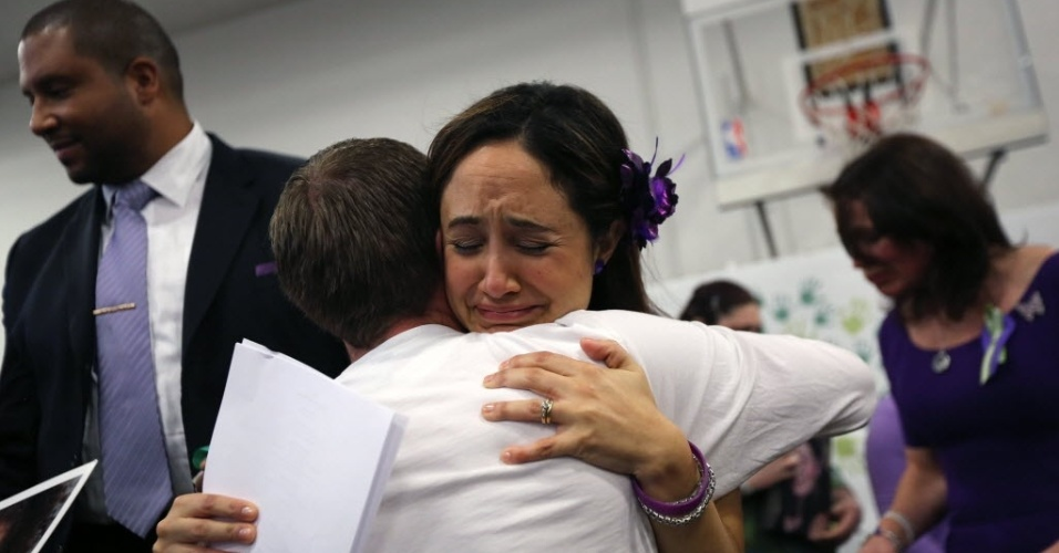 14.jan.2013 - Nelba Marquez Greene, mãe de Ana Grace Marquez Green, 6, uma das vítimas do massacre na escolar primária Sandy Hook, em Newtown, Connecticut (EUA), recebe abraço de amiga, durante coletiva de imprensa na cidade no aniversário de um mês da tragédia