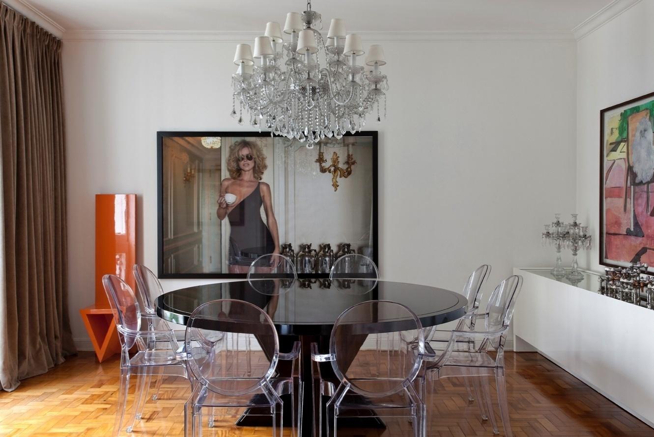 A sala de jantar exibe extrema elegância com mesa de laca preta brilhante, da MiCasa, servida por cadeiras Louis Ghost desenhadas por Philippe Starck e compradas na A Lot Of. O lustre e os castiçais de cristal conferem um toque de época ao espaço que também possui tela de Cristina Canale (à dir.) e aparador-bufê da Casual. Na outra parede, a foto da modelo Eva Herzigova e a cadeira laranja, do arquiteto Aurélio Flores. A decoração do apartamento em São Paulo é assinada por Diego Revollo