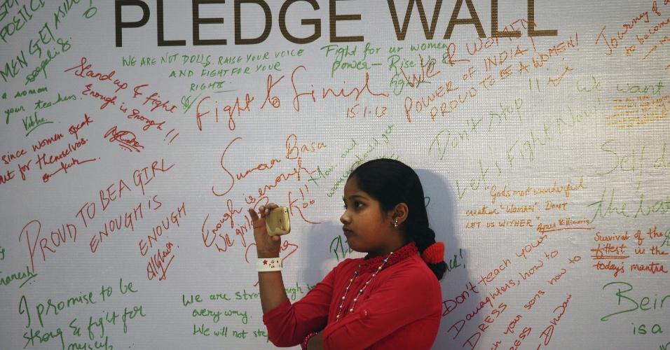 15.jan.2013 - Menina grava vídeo de treinamento de autodefesa perto de parede onde estão escritas frases de repulsa ao estupro de uma estudante indiana de 23 anos, que morreu por conta dos ferimentos