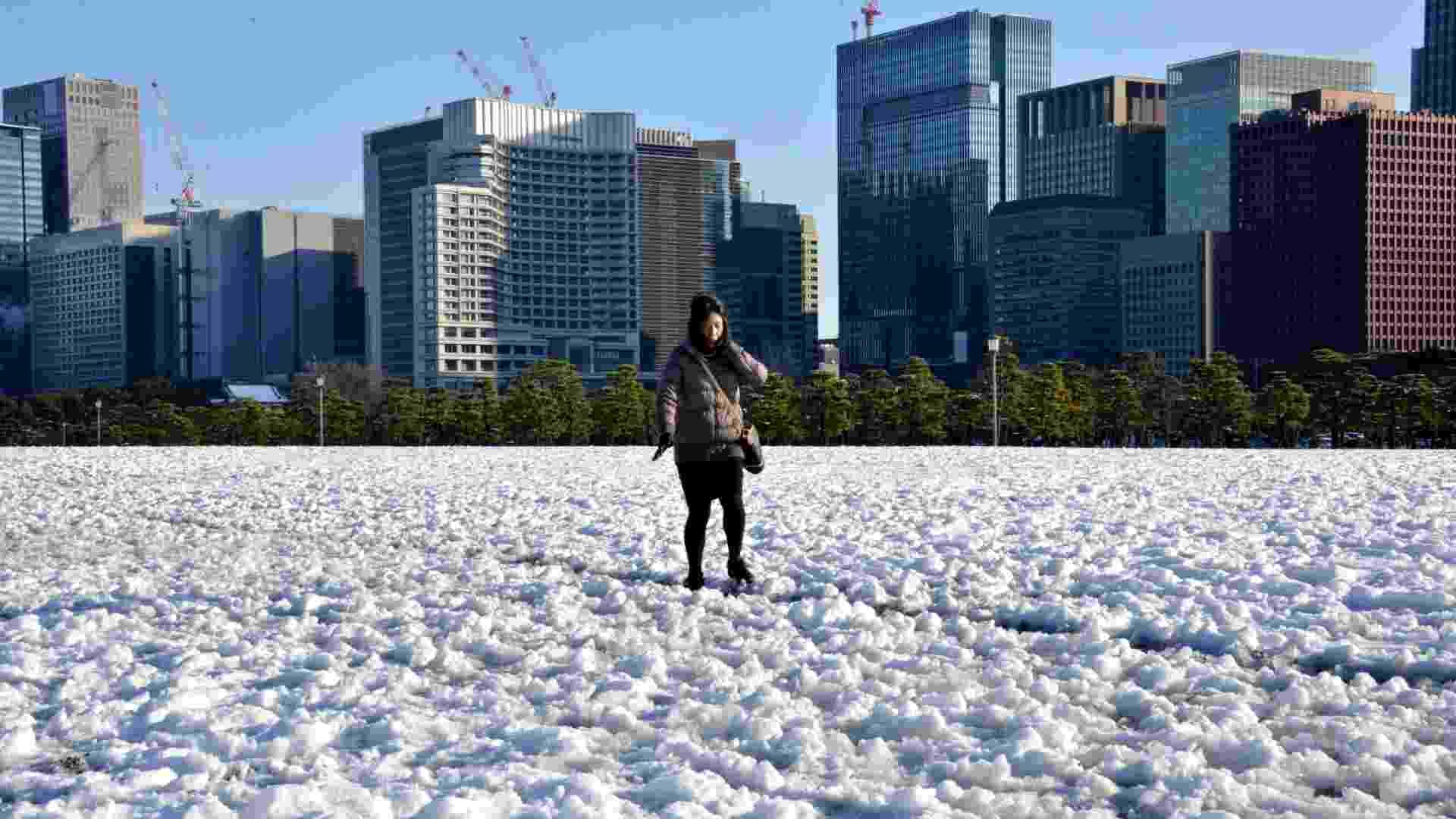 15.jan.2013 - Mulher caminha com cuidado através de um campo coberto de neve no parque diante do Palácio Imperial japonês, um dia após uma forte nevasca atingir a região metropolitana de Tóquio. Uma pessoa morreu e ao menos 463 tiveram ferimentos devido à forte nevasca - Yoshikazu Tsuno/AFP