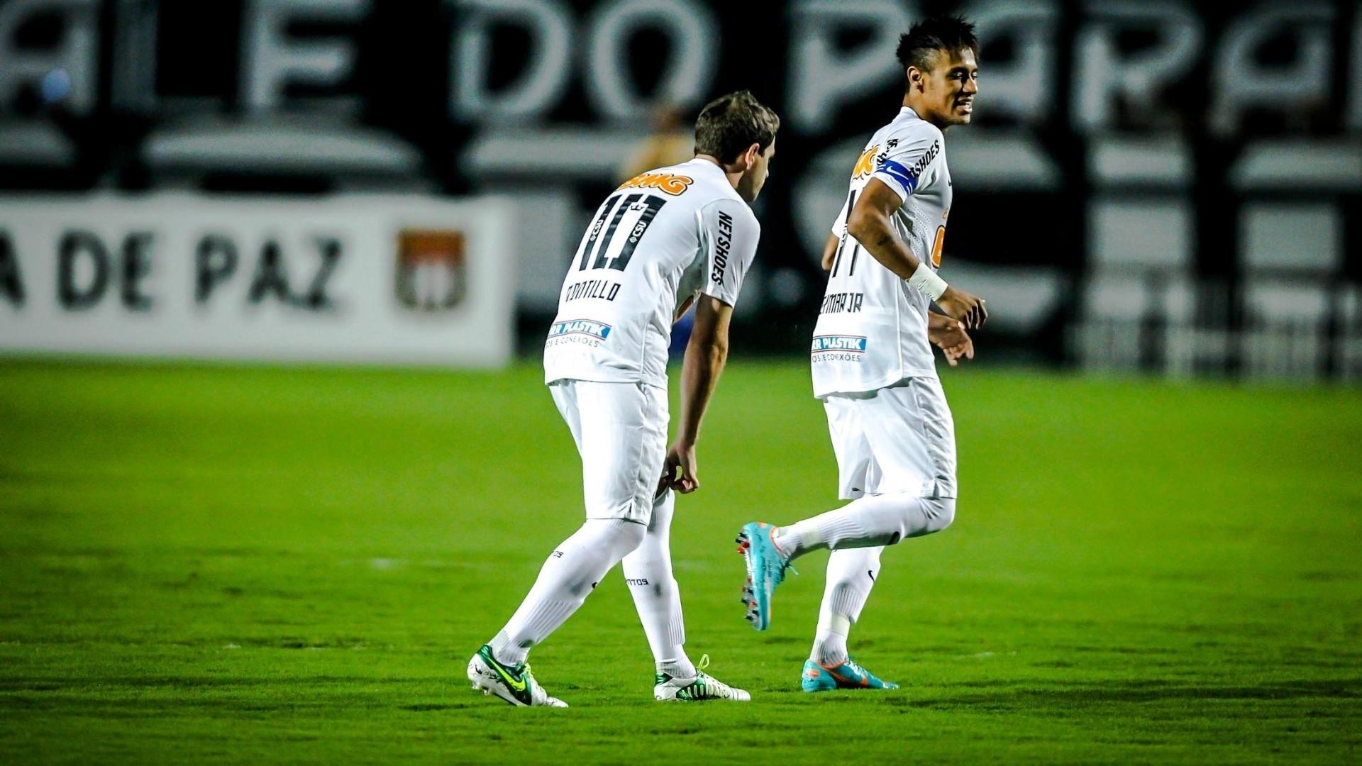 16.jan.2013 - Montillo ajeita a meia enquanto Neymar corre antes de amistoso entre Santos e Barueri