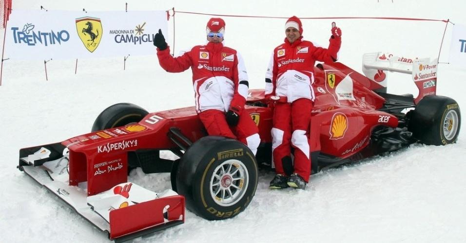 17.jan.2013 - Felipe Massa (d) e Fernando Alonso posam sobre carro da Ferrari durante evento de esqui da equipe na Itália