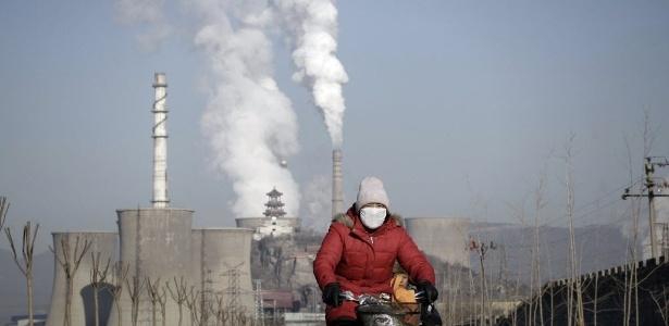 Mulher usando máscara passa de bicicleta por chaminés e torres de resfriamento de usina siderúrgica em Pequim, na China