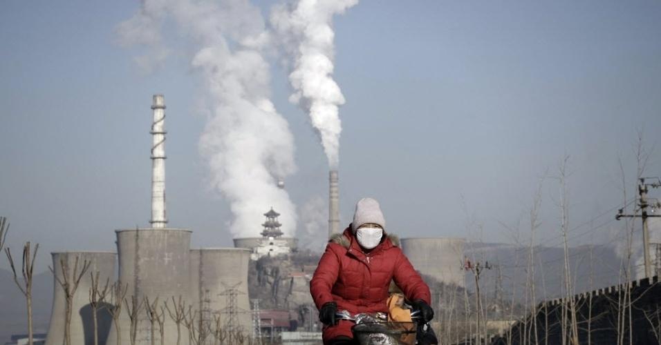 17.jan.2013 - Mulher usando máscara passa de bicicleta por chaminés e torres de resfriamento de usina siderúrgica em Pequim (China). O governo adotou um plano de emergência para tentar baixar os altos níveis de poluição e controlar a má qualidade do ar na capital do país