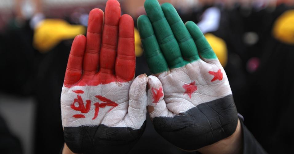 17.jan.2013 - Um manifestante pró-democracia mostra suas mãos pintadas com as cores nacionais da Síria durante uma manifestação em Sanaa, no Iêmen, nesta quinta-feira (17). Os manifestantes exigem diálogo com o presidente Abd-Rabbu Mansour Hadi e o julgamento do ex-presidente Ali Abdullah Saleh, acusado de  crimes de repressão, durante o período  em que esteve no poder