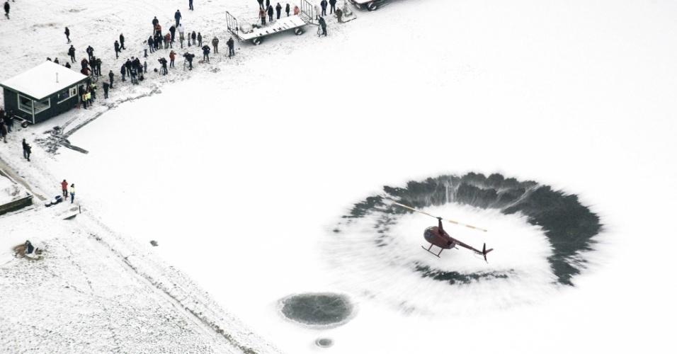 17.jan.2013-  Helicóptero voa próximo ao lago Veluwemer, na Holanda, para tentar remover a neve do local, congelado devido às baixas temperaturas. O helicóptero foi alugado por clubes de patinação que desejam usar o local como pista durante o inverno
