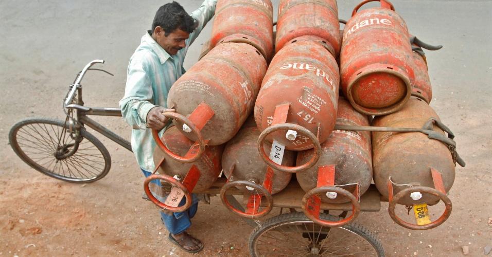 17.jan.2013- Homem coloca butijões de gás em bicicleta para começar as entregas do dia, na Índia