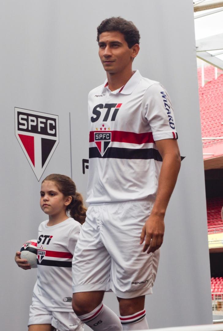 17.jan.2013-Ganso desfila ao lado de garotinha com novo uniforme completo do São Paulo durante evento no bar do Estádio do Morumbi