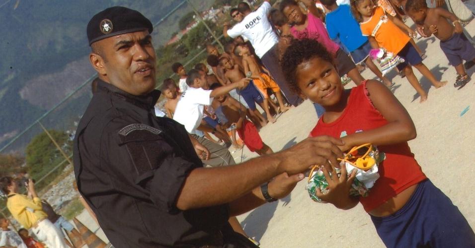 O relações-públicas do Bope (Batalhão de Operações Especiais), major Ivan Blaz, interage com uma menina da favela Cidade de Deus, na zona oeste do Rio, durante o processo de pacificação da comunidade, em 2009.