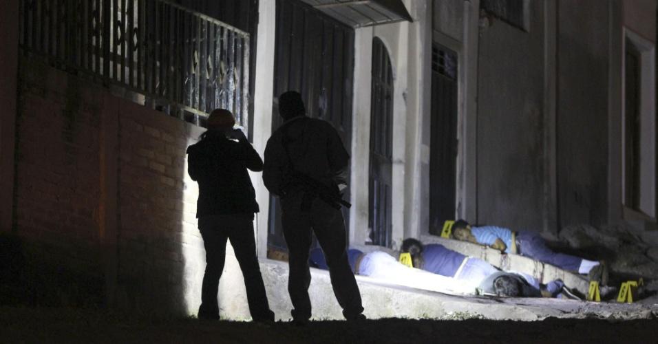 18.jan.2013 - Procuradores forenses e membros da unidade de polícia hondurenha investigam um assassinato de seis pessoas na colônia Ayestas, em Honduras, nesta sexta-feira (18). As pessoas foram mortas a tiros no local por causas ainda desconhecidas, na noite de quinta-feira (17)