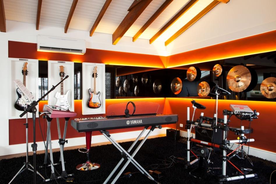 No piso mais alto da casa em Barueri (SP), decorada por Giseli Koraicho, uma grande sala é dedicada ao entretenimento. No ambiente há espaço para carteado, sinuca e música. No teto, as tesouras são aparentes e os rebaixos foram executados em gesso