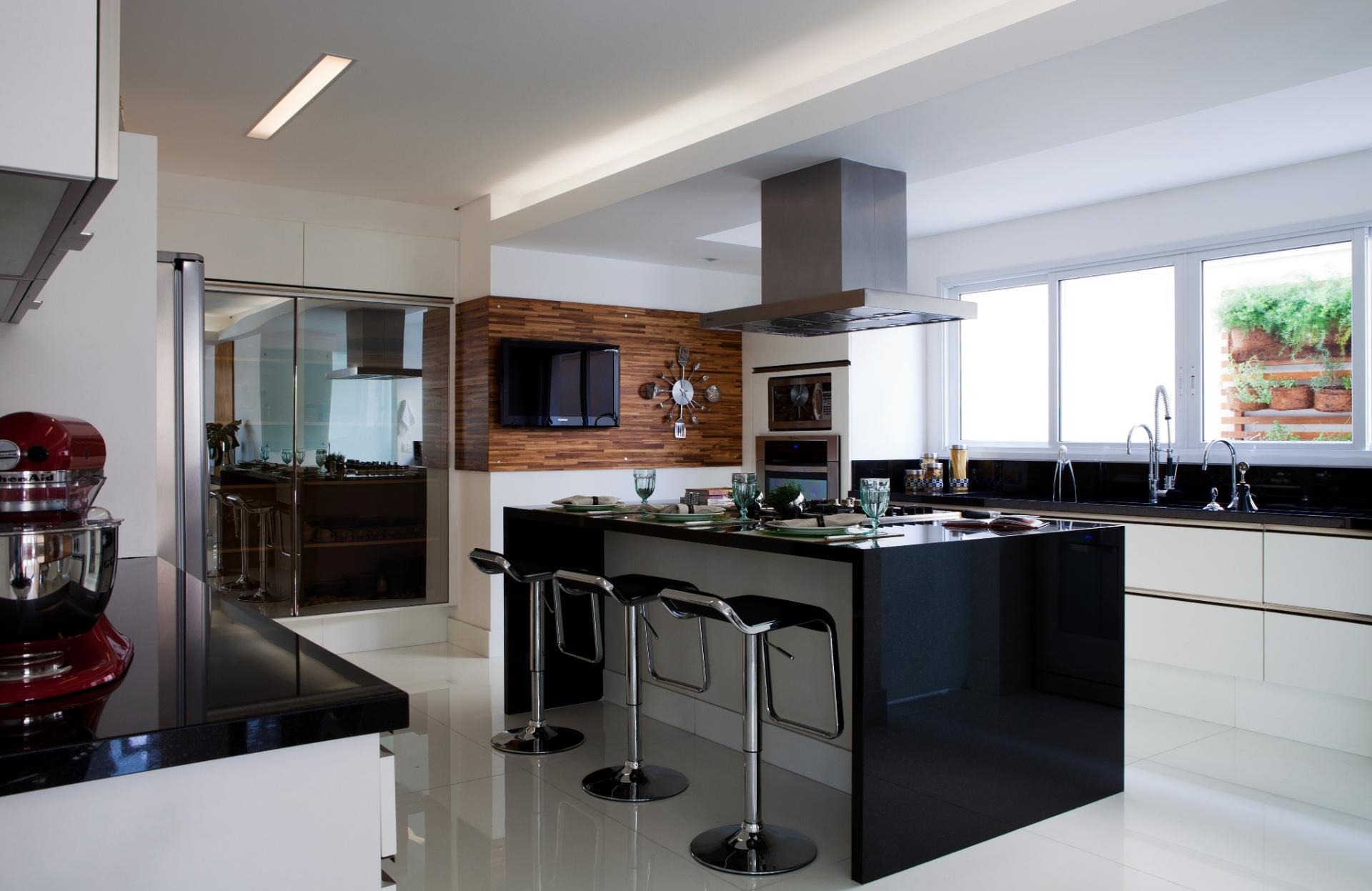Uma ilha de cocção, com espaço para refeições rápidas, foi instalada no centro da cozinha da casa em Barueri (SP), decorada por Giseli Koraicho. O ambiente conta com elementos brancos, pretos, metalizados e em madeira