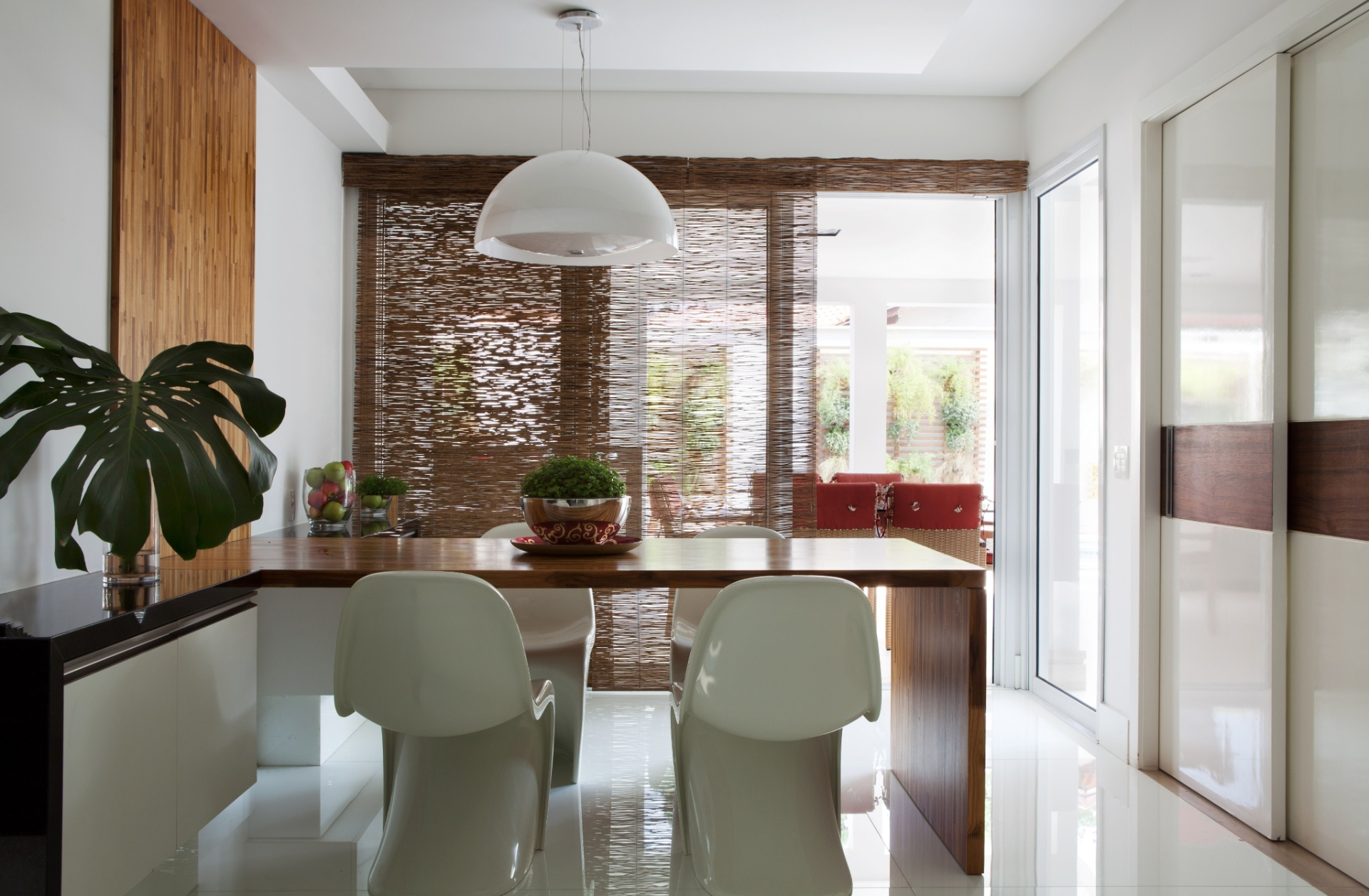 Na casa em Barueri (SP), decorada por Giseli Koraicho, o painel filetado que compõe a mesa e sobe pela parede da área da copa é idêntico ao que a apoia a TV na área de trabalho da cozinha. Ao lado da mesa-bancada, cadeiras Panton