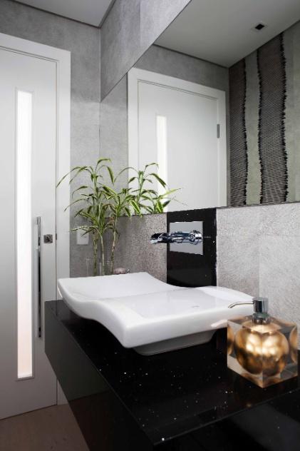 No lavabo da casa em Barueri (SP), decorada por Giseli Koraicho, destaque para o revestimento das paredes feito com papel de parede aveludado e cinzento. No espaço, a bancada que apoia a cuba de louça é feita de Silestone