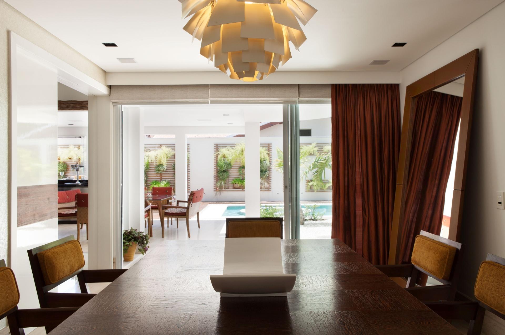 A sala de jantar da casa em Barueri (SP), decorada por Giseli Koraicho, tem mesa e cadeiras da Interni, em madeira, e lustre da Lustreco. O ambiente é interligado à varanda por uma grande porta de vidro