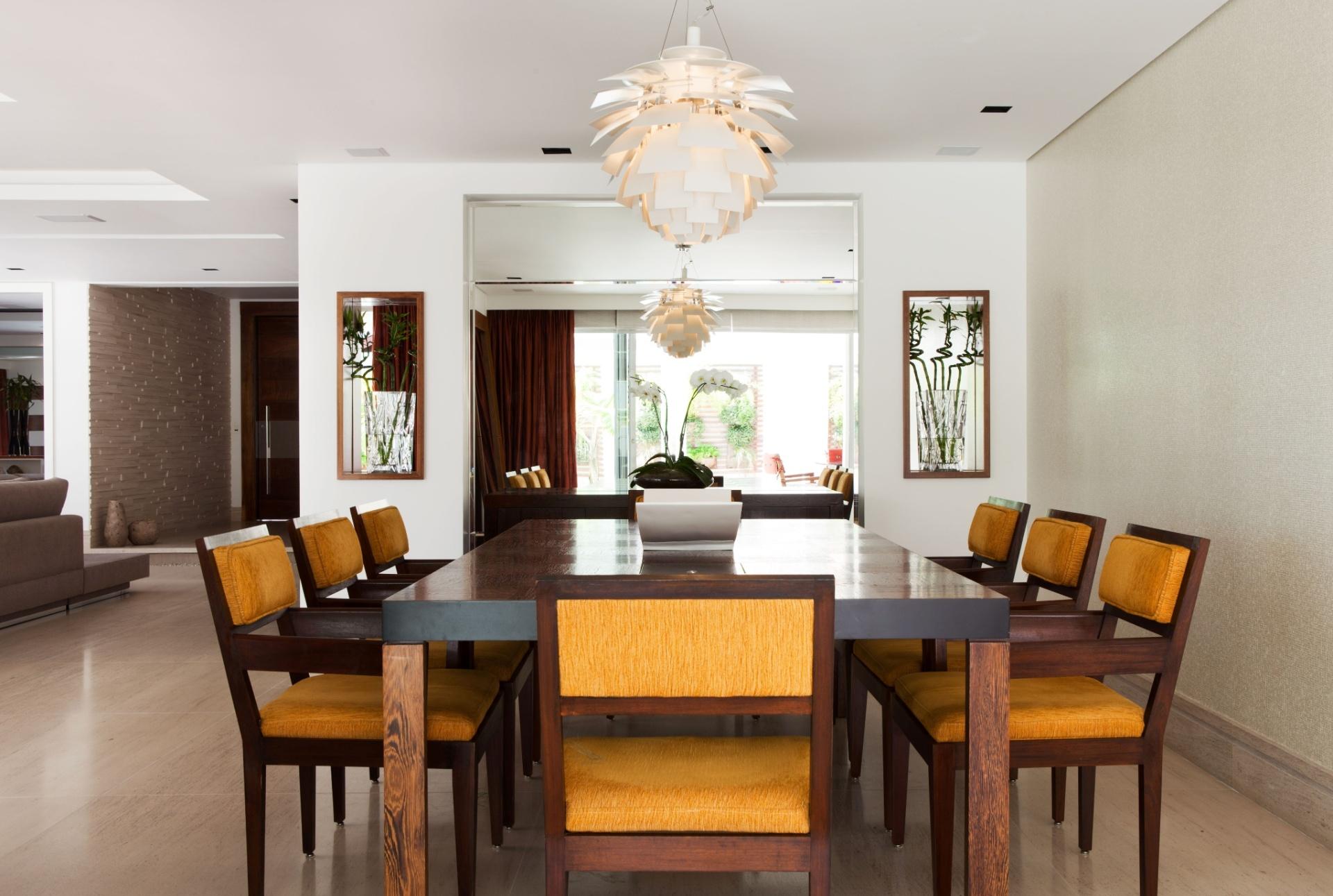 A sala de jantar da casa em Barueri (SP), decorada por Giseli Koraicho, tem mesa e cadeiras da Interni, em madeira, e lustre da Lustreco. Destaque para os espelhos generosos, inclusive nos nichos que sustentam os vasos, que ampliam ainda mais o ambiente