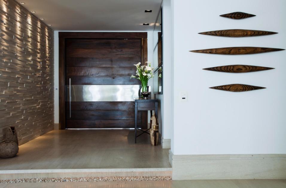No hall de entrada da casa em Barueri (SP), decorada pela designer de interiores Giseli Koraicho, há uma maciça presença de madeira na ampla porta pivotante, bem como nos móveis e objetos. Destaque ainda para a parede com volumetria, à esquerda