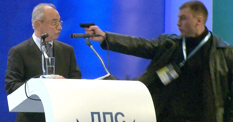 19.jan.13 - Imagem capturada de vídeo da TV búlgara BTV mostra homem apontando arma para Ahmet Dogan, líder do partido MRF (movimento pelos direitos e liberdade, em tradução livre), que representa a minoria turca na Bulgária. A tentativa de homicídio aconteceu durante um evento, em Sófia, neste sábado (19)