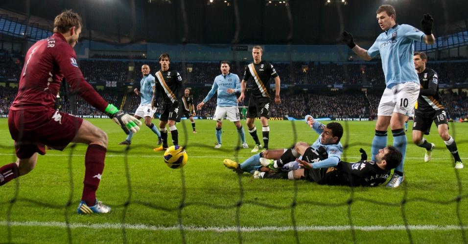 19.jan.2013 - Carlos Tevez, do Manchester City, tenta a finalização, mas para na defesa do goleiro Mark Schwarzer, do Fulham