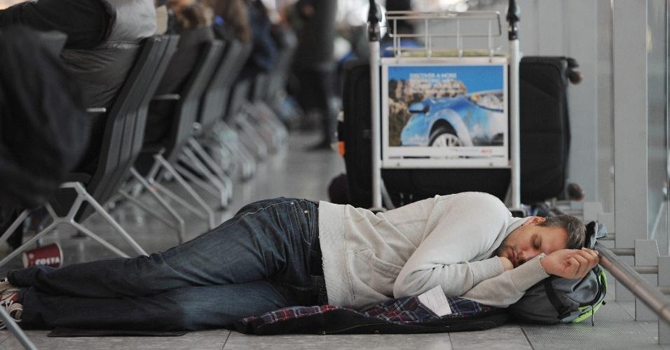 Homem dorme no piso do aeroporto de Heathrow, em Londres, após mais de 100 voos serem cancelados em função do mau tempo
