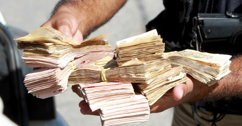 Policial mostra R$ 25 mil em dinheiro vivo recuperados após explosão de caixa eletrônico na cidade de Taquaraçu de Minas, na região central do Estado de Minas Gerais