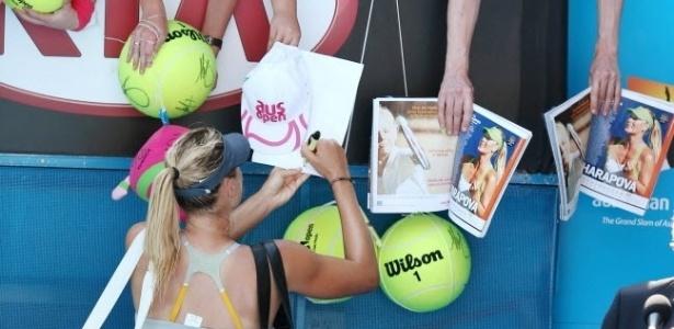 20.jan.2013 - Maria Sharapova autografa objetos de fãs após se classificar para as quartas de final com mais um atropelamento