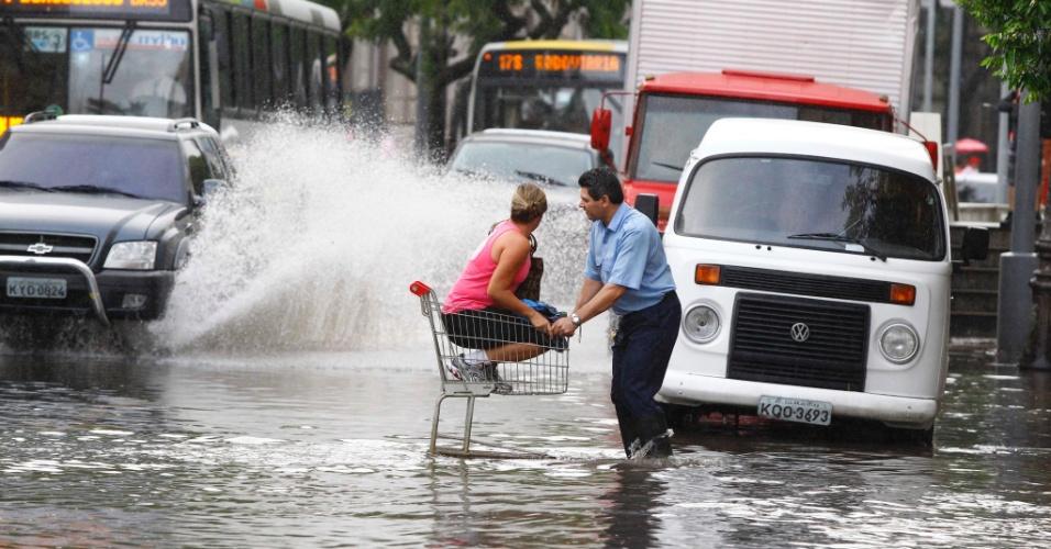 22.jan.2013- Várias ruas do Rio de Janeiro ficaram alagadas após as fortes chuvas da madrugada, complicando também o trânsito em vários pontos da cidade. Para fugir do alagamento na rua do Catete, na zona sul, uma mulher chegou a ser carregada em um carrinho de compras