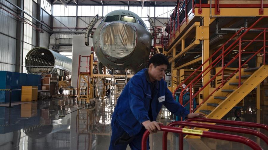 Funcionário passa por Airbus A320 em fase de montagem na fábrica da empresa em Tianjin, na China - Sim Chi Yin / The New York Times