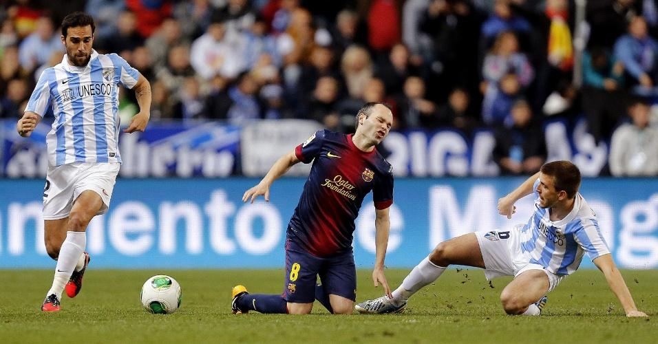 24.jan.2013 - Iniesta (centro), meio-campista do Barcelona, cai após sofrer falta de jogador do Málaga, durante jogo válido pelas quartas de final da Copa do Rei