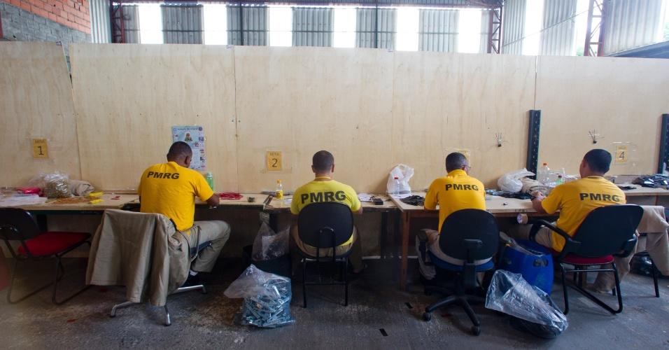 24.jan.2013 - Presos trabalham em linha de montagem de equipamentos eletrônicos dentro do presídio. Eles recebem um salário mínimo (R$ 678) por mês. O dinheiro é dividido entre o interno, sua família, outros presos e o Estado
