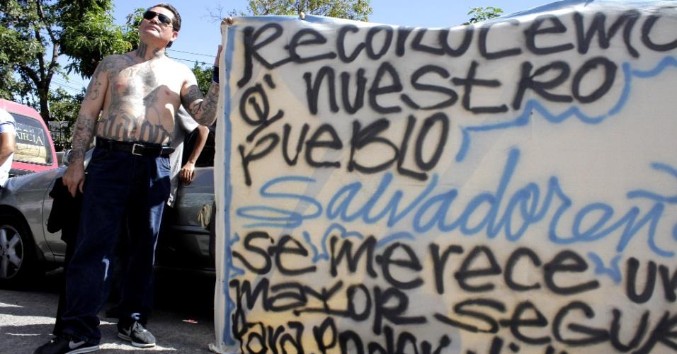 24.jan.2013 - Membro da gangue Mara Salvatrucha segura cartaz durante ato declarando Santa Tecla, na região metropolitana de San Salvador, como segundo município livre da violência das maras, violentas e grandes gangues de El Salvador. Em março de 2012, as duas principais maras, Salvatrucha e 18, anunciaram uma trégua. Calcula-se que o acordo poupou a vida de 1.600 pessoas entre março e novembro desse ano