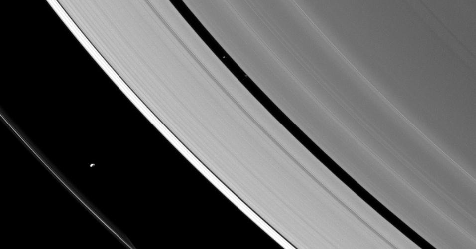 """25.jan.2013 - A sonda Cassini fez mais um novo registro """"artístico"""" de Saturno ao fotografar duas das 60 luas conhecidas do planeta no meio do seu sistema de anéis. A lua Prometheus (canto inferior, à esquerda) tem cerca de 86 quilômetros de diâmetro e fica mais próxima do anel exterior F, enquanto os 28 quilômetros de diâmetro de Pan ficam """"espremidos"""" no intervalo do anel A, mais próxima de Saturno - o pequeno ponto abaixo dela, com menor brilho, é uma estrela do céu. O registro foi feito em setembro do ano passado, mas divulgado apenas agora pela Nasa (Agência Espacial Norte-Americana)"""