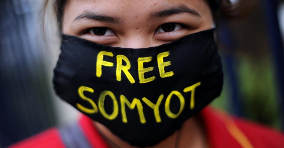 25.jan.2013 - Ativista veste uma máscara com a frase 'libertem Somyot' durante protesto diante da corte criminal da Tailândia, em Bancoc. Os manifestantes pedem a libertação do jornalista Somyot Prueksakasemsuk, condenado nesta quarta-feira (23) a 11 anos de prisão por publicar dois artigos críticos à monarquia do país