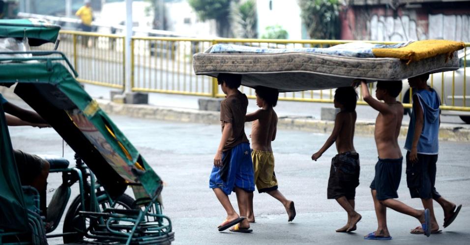 25.jan.2013 - Crianças sem teto carregam colchão em rua de Manila (Filipinas). O presidente do país, Benigno Aquino, assinou, em 19 de dezembro, uma lei aumentando impostos sobre álcool e tabaco, prevendo um crescimento de US$ 49 bilhões no orçamento, que deverão ser revertidos para programas de redução da pobreza