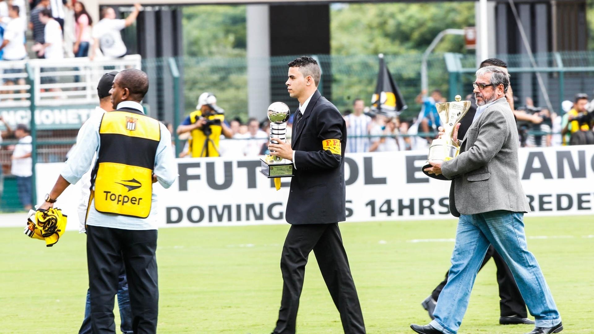 25.jan.2013 - Delegado da FPF leva a taça da Copa SP para o gramado