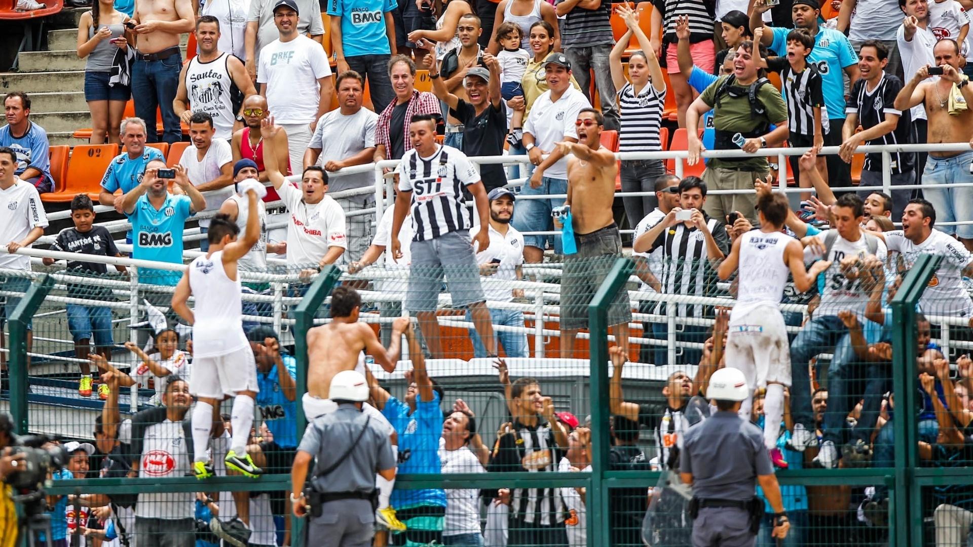 25.jan.2013 - Jogadores do Santos pulam no alambrado do Pacaembu para comemorar a conquista da Copa SP com a torcida